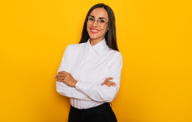 Modern happy successful confident business woman in a white shirt eyeglasses is posing on yellow background