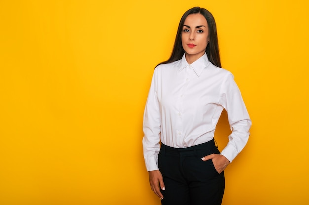 Modern happy successful confident business woman in a white shirt is posing on yellow background