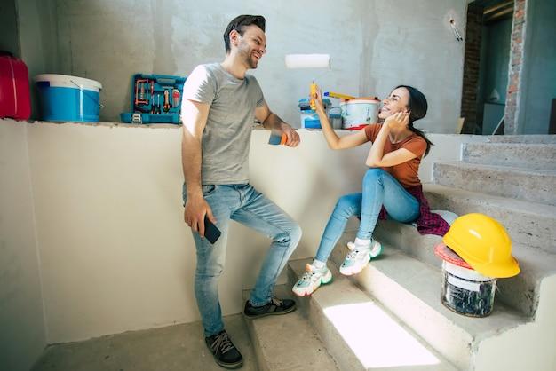 새로운 집 수리 또는 이것에 대한 많은 도구로 벽을 개조하는 동안 캐주얼 옷에 사랑에 현대 행복 젊은 부부