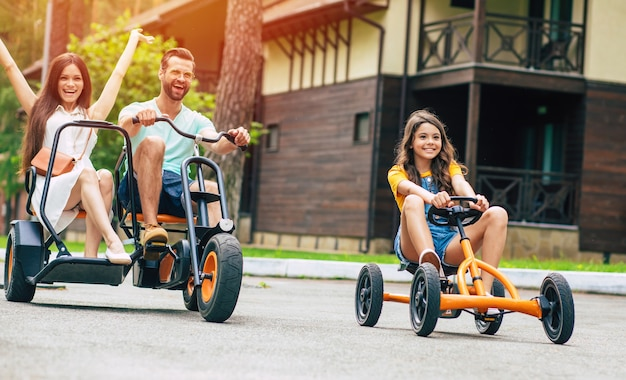 Modern happy young tourist family on vacation riding on bikes and have fun together