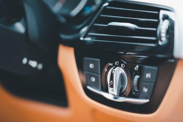 現代の車のコックピットにある現代のヘッドライトスイッチは、コピースペースでクローズアップします。エアコングリル付きステアリングホイール横のダッシュボードにある自動車両ヘッドライトコントローラーパネル。