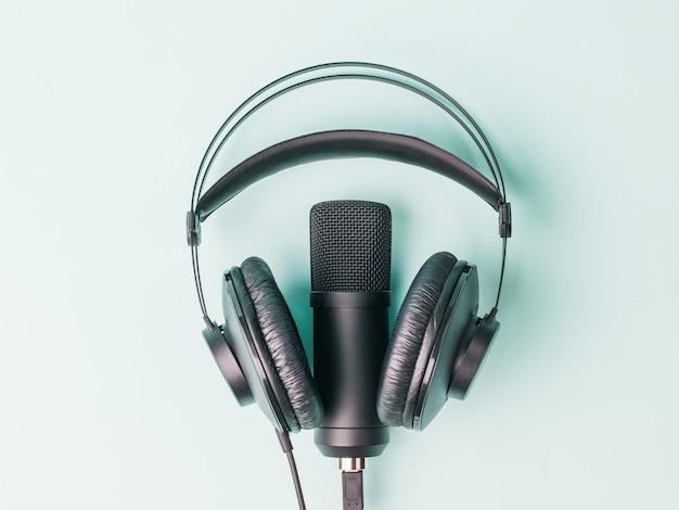 Современные наушники и микрофон на синей поверхности