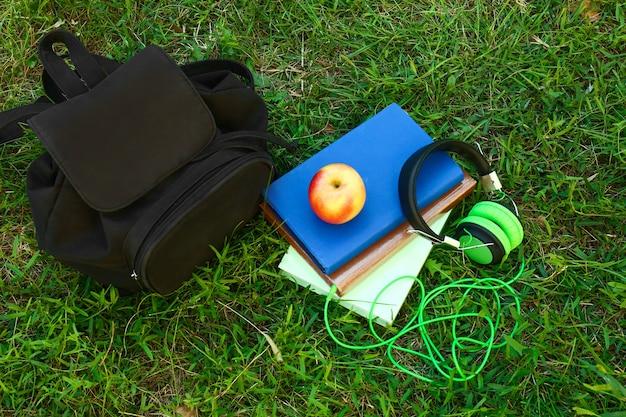 Современные наушники, сумка и книги на зеленой траве. концепция аудиокниги