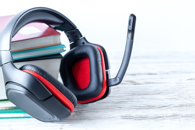 Modern headphones and books on table on white background. concept of audiobook.