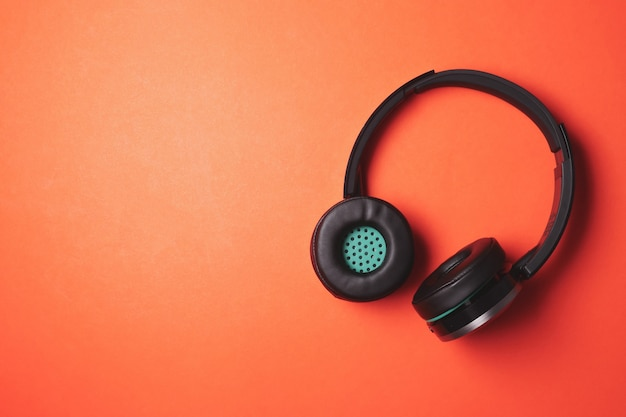 Modern headphones on a orange background. free space for text