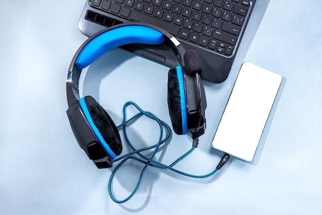 파란색 배경에 현대적인 헤드폰, 전화 및 노트북이 평평하게 놓여 있습니다.