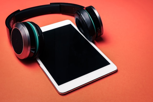 Modern headphones with tablet pc on a orange background.