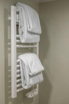 在卫生间墙壁上的现代加热的毛巾铁轨。现代白色加热毛巾轨道