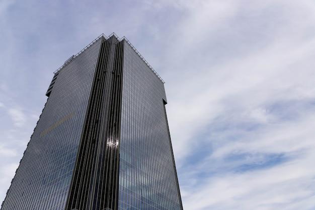 空を背景にしたモダンな高層オフィスビル、超高層ビル。
