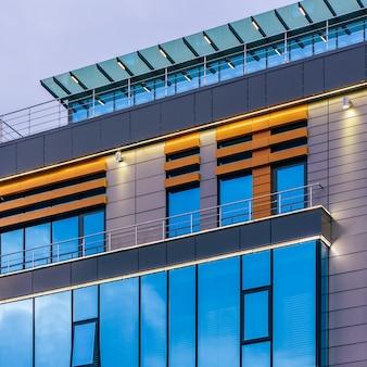 흐린 배경에 유리 외관이 있는 현대적인 고층 사무실 건물입니다.