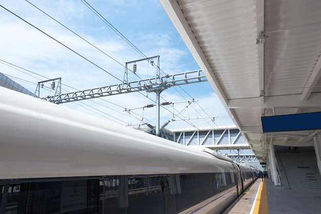 Modern high speed train at the railway station with motion blur effect