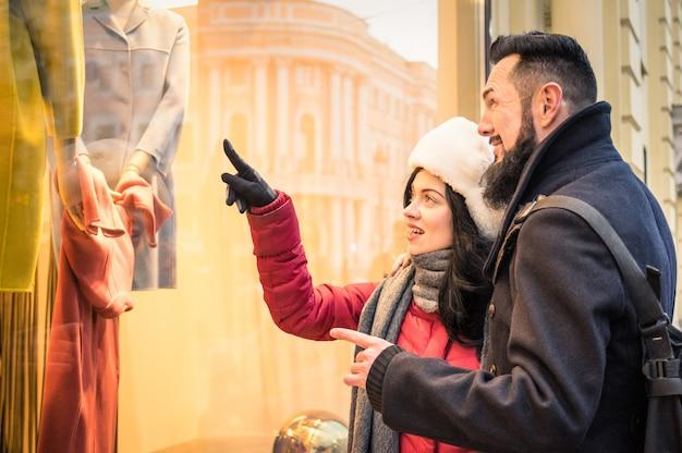 冬の布ポインティングモーダストアウィンドウディスプレイで買い物をする現代の流行に敏感なカップル