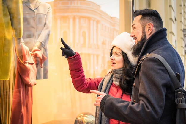Modern hipster couple shopping on winter cloth pointing moda store window display