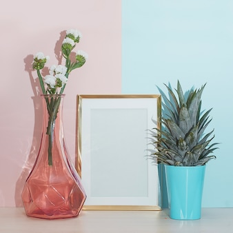 Modern home decor mock up with wooden photo frame, vase and tropical plant on pink blue ba