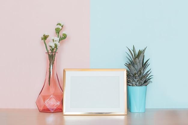 Современный домашний декор с золотым макетным фоторамкой, вазой и тропическим растением на розовой синей спине