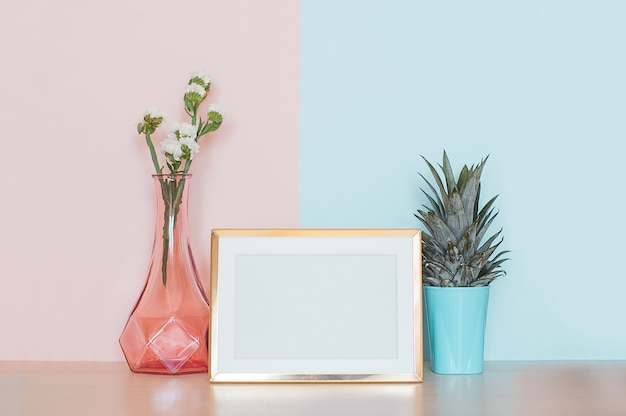 Modern home decor with gold mock up photo frame, vase and tropical plant on pink blue back