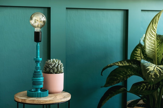 Modern home interior of bedroom with design coffee table, table lamp, succulent and beautiful plant. green wall panelling. stylish home staging. template. close up.