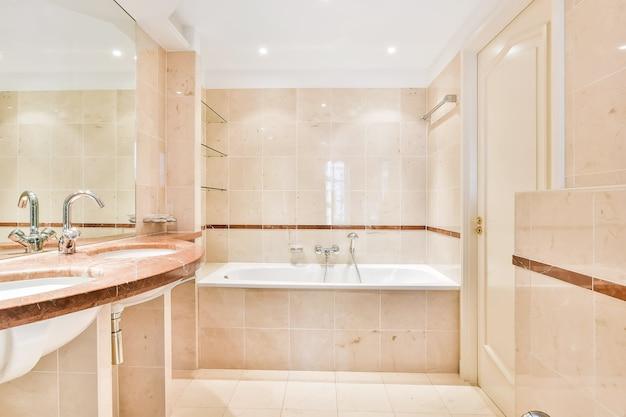 흰색 세라믹 타일과 샤워기가있는 욕조가있는 밝은 욕실의 현대적인 홈 인테리어 디자인