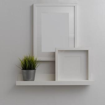 흰 벽에 흰색 선반 위에 모형 프레임과 식물 냄비와 현대 홈 인테리어 디자인