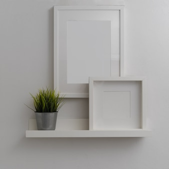 Modern home interior design with mock-up frames and plant pot above white shelf on white wall