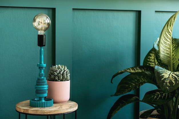 Современный домашний интерьер спальни с дизайнерским журнальным столиком, настольной лампой, сочными и красивыми растениями. зеленая вагонка. стильная домашняя постановка. шаблон. закройте вверх.