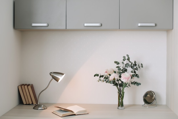 モダンな家のインテリア。本と花の木製の机。計画と設計のコンセプト。職場。フェミニンなフラットレイ。