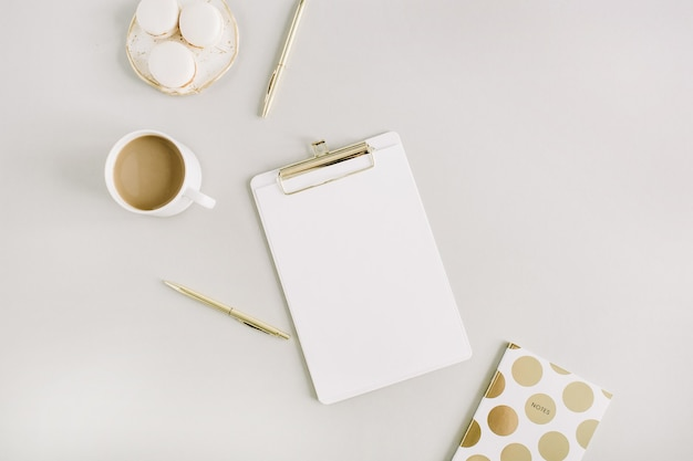 Modern home office desk with clipboard, macaroons, pen, coffee mug on pastel background. flat lay, top view