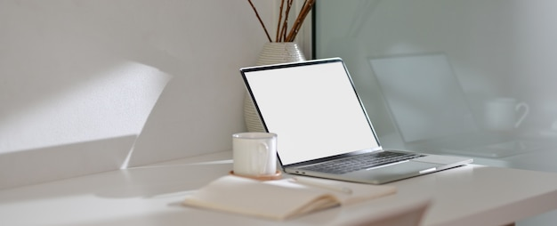 Modern home office desk with  laptop, notebook, cup and decoration