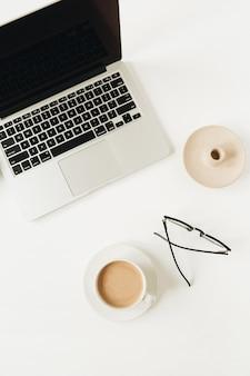 Современный домашний офисный стол с ноутбуком, чашкой кофе, очками на белой поверхности