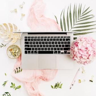 Современное рабочее место стола домашнего офиса с компьтер-книжкой, различными цветами и растениями и аксессуарами на белой поверхности. плоская планировка, вид сверху