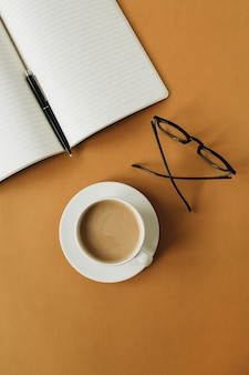 ノートブック、一杯のコーヒー、生姜の表面にグラスを備えたモダンなホームオフィスデスクワークスペース
