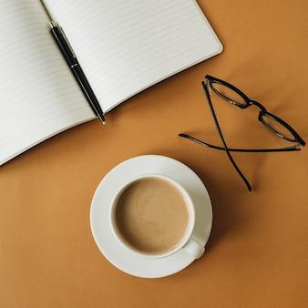 ノートブック、一杯のコーヒー、生姜のグラスとモダンなホームオフィスデスクワークスペース