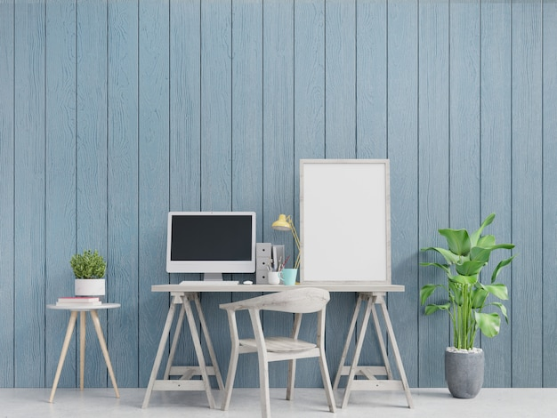 Modern home office interior with blue walls and a framed vertical poster.