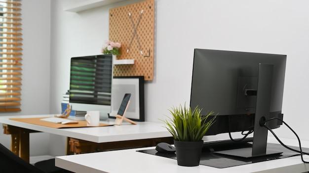 Интерьер современного домашнего офиса с компьютерами и канцелярскими товарами.