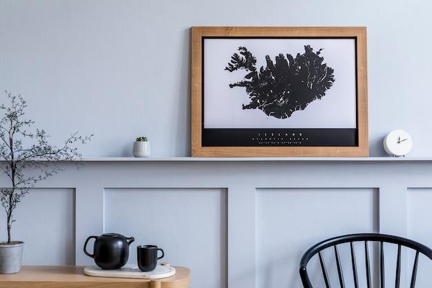 Современная домашняя обстановка гостиной с дизайнерским стулом, деревянной консолью, чайником, цветком, книгами, декоративным макетом в рамке для плаката и элегантными личными аксессуарами.