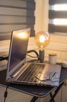 Modern home workplace of freelancer with yellow lamp and laptop on black table