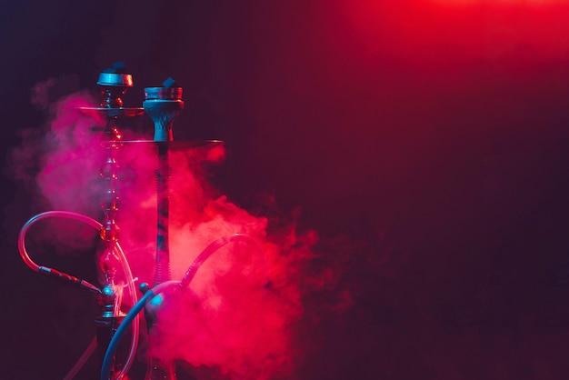 Современный кальян, кальян на дымно черном фоне с цветным освещением и дымом. крупный план и место для текста