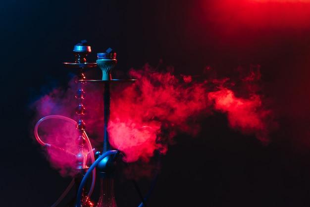 Современный кальян, кальян на дымно черном фоне с неоновым освещением и дымом. место для текста