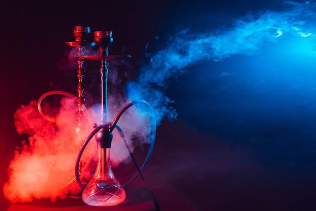 Modern hookah, shisha on a smoky black background with neon lighting and smoke.
