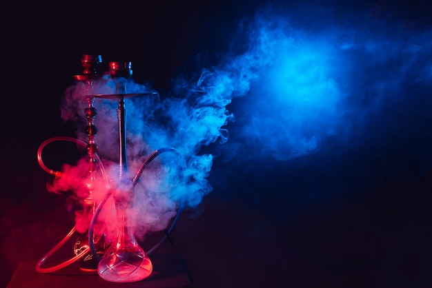 Modern hookah, shisha on a smoky black background