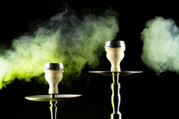 Modern hookah with smoke in dark club light