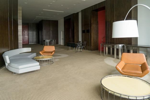 Современный вестибюль отеля с кожаным диваном и стульями, лампой и круглыми столами.