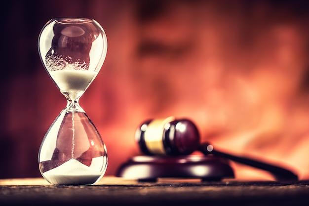 Современные песочные часы во время бега и молот правосудия на деревянном столе.