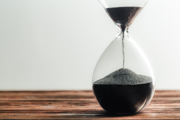 Modern hourglass on wooden surface
