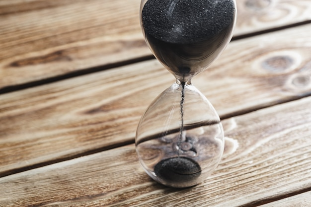 Modern hourglass on wooden table