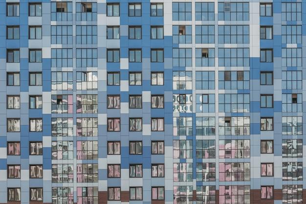 Современный дом в голубых тонах с множеством окон.