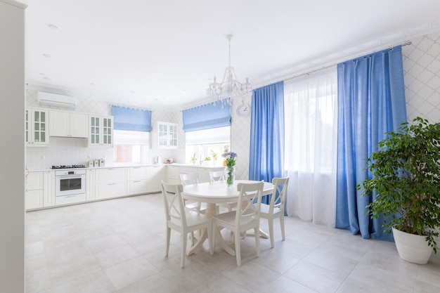 Modern house interior of spacious bright kitchen and dining room with white furniture and blue curtains