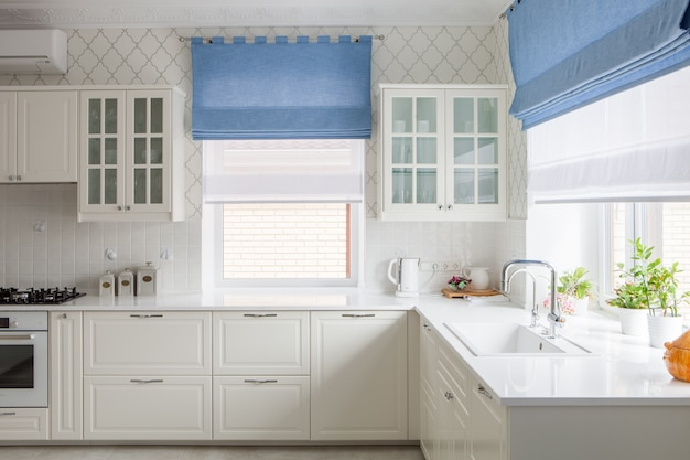 Modern house interior of spacious bright kitchen with white furniture. window blue curtains behind the sink