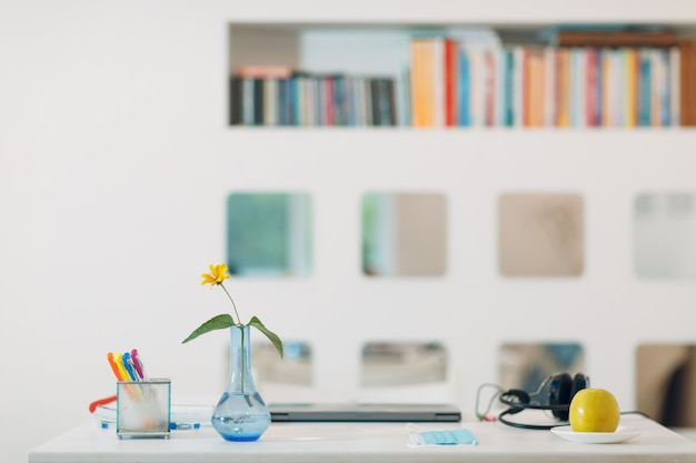 白い壁の背景と本棚とテーブルの上に銀のラップトップ、ヘッドフォン、花瓶、花、リンゴ、フェイスマスクとペンを備えたモダンな家のインテリアワークスペース。