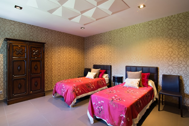 Modern house room, with wallpaper and two single beds with fuchsia duvets. decorative ceiling.